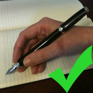 A hand holding a pen in a relaxed grip, with a green checkmark in the corner
