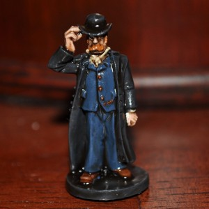 a painted miniature of a man in a suit, bowler hat, and trench coat