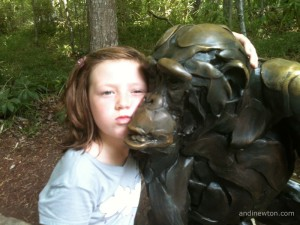 Savannah leans in close to a monkey statue and makes her best monkey face