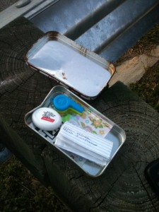 An open metal tin, filled with paper, a sheet of stickers, a blue plastic whistle, and a roll of dental floss