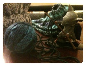 A MouseGuard figurine with a ball of yarn, some tangled around his staff, and a partially knitted hat