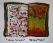 A knitted book, open to two pages. The page on the left is white with splatters of gray, red, and brown. The page on the right has copper, red, brown, and green at the top. The green bleeds down into yellow in the middle, ending with dark red at the bottom. The book cover is mottled dark brown.